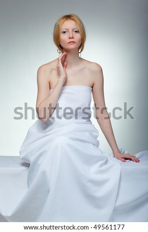 Beautiful young woman in towel sitting - stock photo