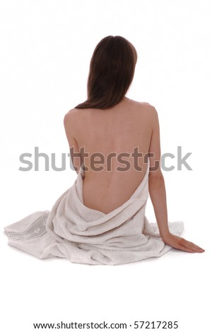 Beautiful young woman in towel sitting on the floor in the white background