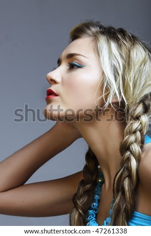 beautiful young woman in turquoise dress with long blond braids - stock photo