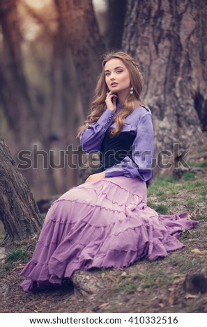 Beautiful young woman in vintage purple dress and white hat walks in the park in early spring - stock photo