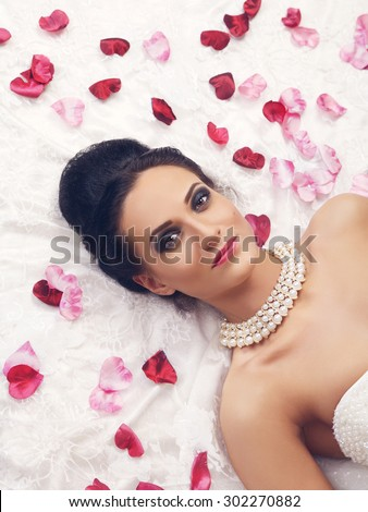 beautiful young woman in wedding dress lying on bed with rose petals - stock photo