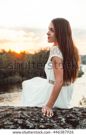 Beautiful young woman in white dress in golden sunshine glow of sunset enjoying peace, serenity in nature. Girl portrait with long hair relaxing on sunset light outdoors. Soft warm sunny colors. - stock photo