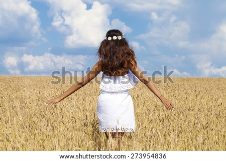 Beautiful young woman in white dress on wheat golden field - stock photo