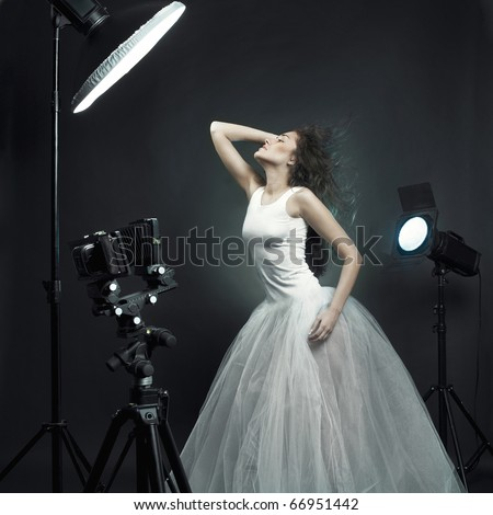 Beautiful young woman in white dress pose in photo-studio