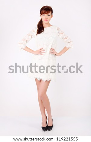Beautiful young woman in white openwork dress holds by waist and looks at camera.