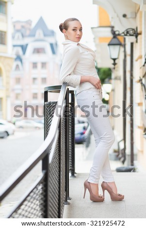 Beautiful young woman in white pants and jacket posing outdoors - stock photo