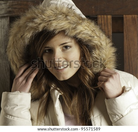 Beautiful young woman in white parka warms up after being outdoors. - stock photo