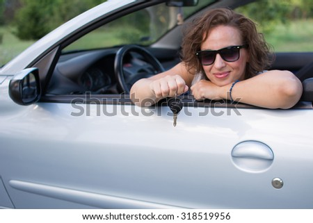 Beautiful young woman in white shirt and black glasses, smiling from a car with car key. She bought a new car. She is happy. Focus is on the car key.