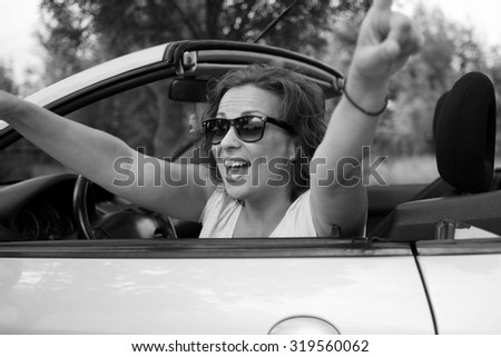 Beautiful young woman in white shirt and black glasses, smiling from a car with open hands. Black and white photo. Focus on face .
