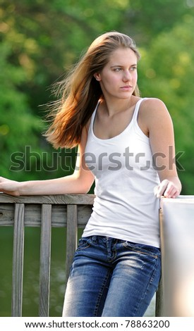 Beautiful young woman in white tank top leaning against a dock railing with morning sunlight highlighting her hair - looking off frame - stock photo