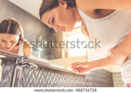 Beautiful young woman in white undershirt is holding a pregnancy test, keeping one hand on her stomach and leaning forward feeling pain, standing in the bathroom