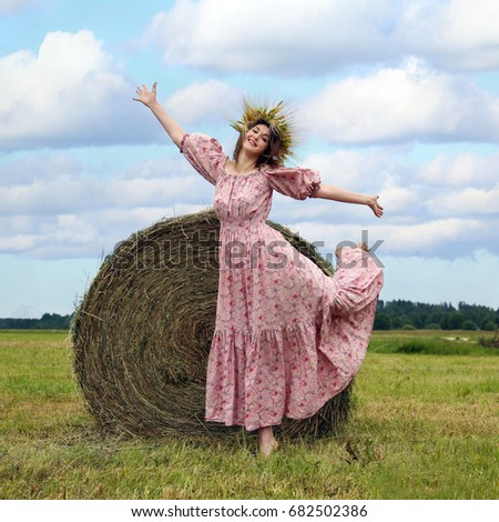 Beautiful young woman in wreath of cereal spikes on head dances in front of straw bale in field under blue cloudy sky - square