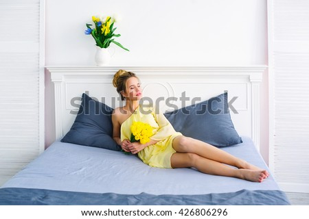 Beautiful young woman in yellow dress posing with bunch of fresh tulips on her bed - stock photo