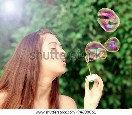 Beautiful young woman inflating colorful soap bubbles in pure nature