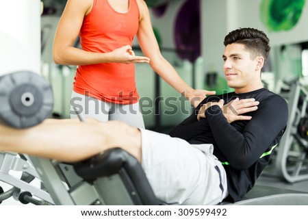 Beautiful young woman instructing a young man in the gym and overlooking his workout - stock photo
