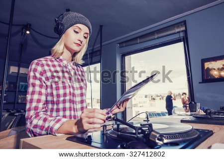 beautiful young woman is browsing and listening a record in the vinyl record store - stock photo