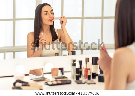 Beautiful young woman is doing makeup using a lip gloss and smiling while looking at the mirror - stock photo