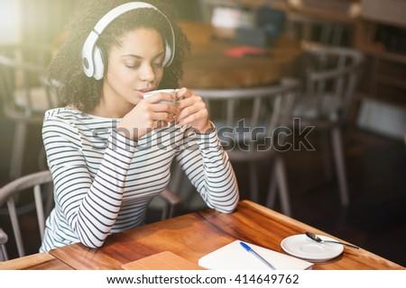 Beautiful young woman is enjoying hot drink - stock photo