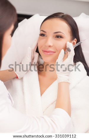Beautiful young woman is getting botox injection in her face. She is sitting and smiling. The female doctor is checking her skin with concentration and holding syringe - stock photo