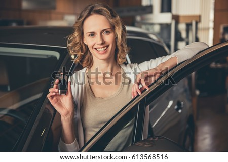 Beautiful young woman is holding a key, looking at camera and smiling while standing near the new car in car dealership