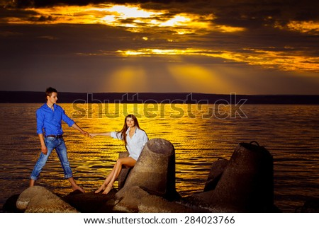Beautiful young woman is holding her boyfriend by hand at a stunning golden seascape sunset background.