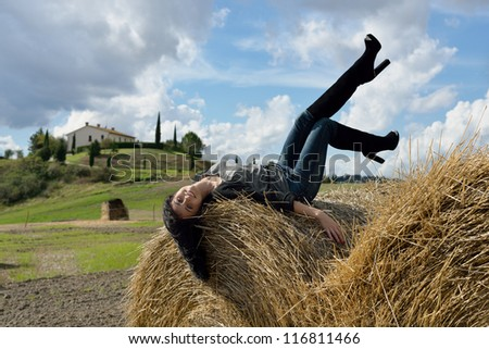 Beautiful young woman is lying on stack of hay on sunny day in the country, Tuscan, Italy - stock photo