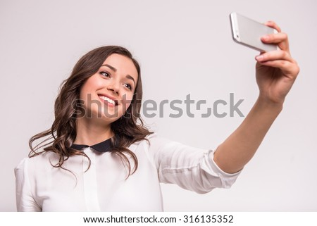 Beautiful young woman is making selfie photo with smartphone. - stock photo