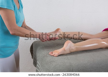 Beautiful young woman is ready for foot  massage at  spa