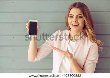 Beautiful young woman is showing a smartphone, looking at camera and smiling, standing against gray background - stock photo