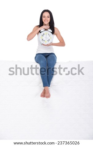 Beautiful young woman is sitting on mattress with clock, isolated on a white background. - stock photo