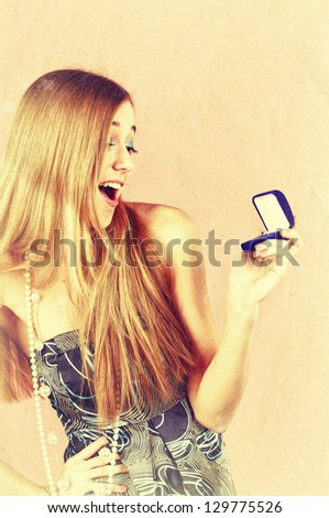 Beautiful young woman is surprised by an engagement ring in the opened gift box. Retro style image. - stock photo