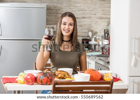 Beautiful young woman is toasting with red wine at holiday dinner party at home. She is smiling and looking at camera.