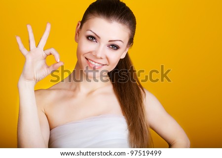Beautiful young woman isolated on yellow background - stock photo