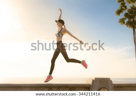 Beautiful young woman jumping and exercise close to the sea with sunset behind her. Golden colors made nice feeling and matching with long blonde hair of the girl.  - stock photo