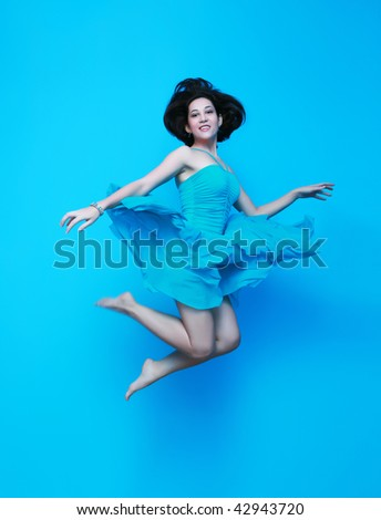 beautiful young woman jumping in blue dress - stock photo