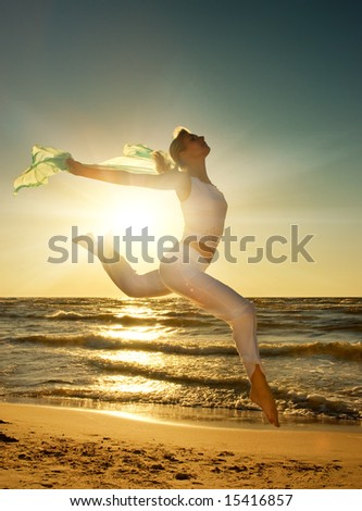 Beautiful young woman jumping on a beach at sunset - stock photo