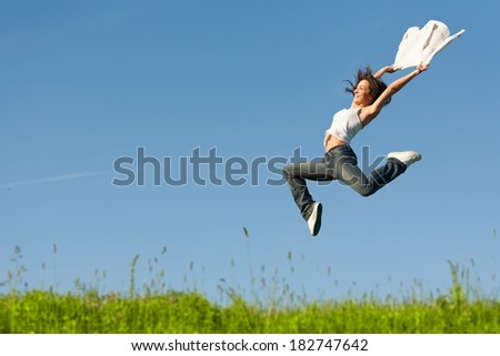 Beautiful young woman jumping on a green grass with a white shirt