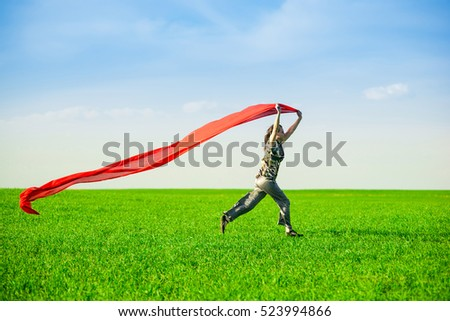 Beautiful young woman jumping on a green meadow with a colored red tissue. Happy female in wheat field with fabric. Summer picnic and freedom concept.