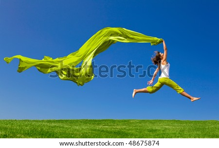 Beautiful young woman jumping on  a green meadow with a colored tissue - stock photo