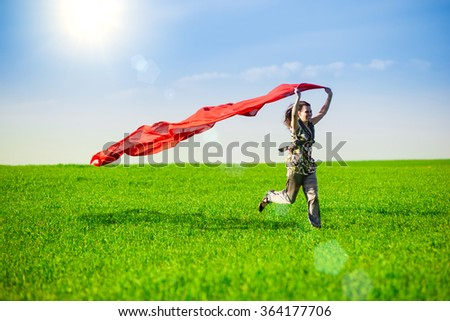 Beautiful young woman jumping on a green meadow with colored tissue - stock photo