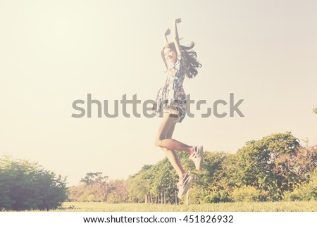 beautiful young woman jumping on green grass