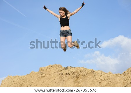 beautiful young woman jumping up background summer blue sky clouds