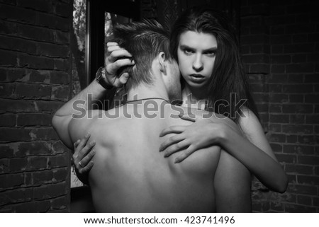Beautiful young woman kissing her boyfriend while standing near brick wall in loft interior
