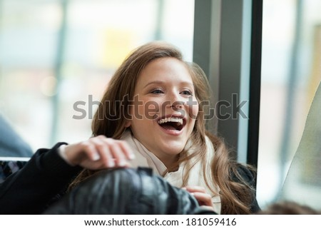Beautiful young woman laughing in bus