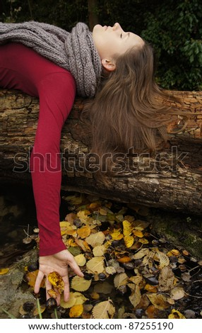 Beautiful young woman laying on a tree trunk touching fallen leaves - stock photo