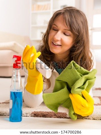 Beautiful young woman laying on the floor after cleaning her house wearing yellow gloves with spray cleaners and cloth - stock photo