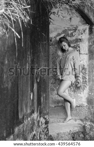 Beautiful young woman lean on the wall - black and white - stock photo