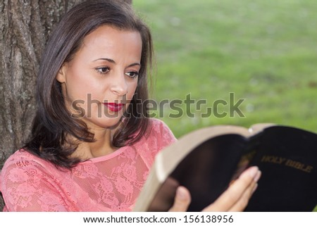 Beautiful young woman leaning on tree and reading bible - stock photo