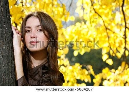 Beautiful young woman leaning to tree trunk in yellow autumn park. - stock photo