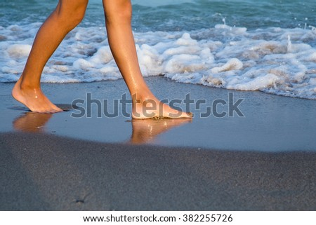 Beautiful young woman legs on the beach at sunset